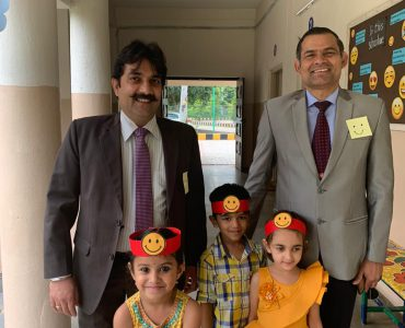 8.Our Principal Mr. Skand Bali & Mr. Sharma registerar with tiny tots smiling.